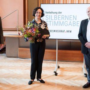 Verleihung der Silbernen Stimmgabel des Landesmusikrats 2021 an Marieddy Rossetto (Mitte) durch Holger Müller (links); die Laudatio hielt Rolf Kessler (rechts) ©vlago